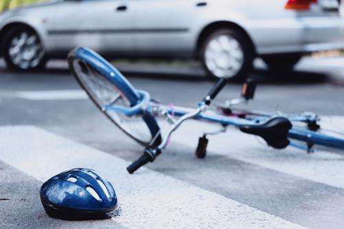 A bicycle and helmet lying on asphalt after an accident with a car.