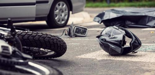 A motorcycle and helmet lying in a street after an accident with a car.