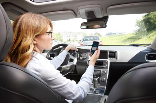 A woman texting while driving.