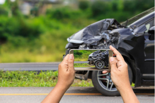 Woman taking photo of car after wreck with phone