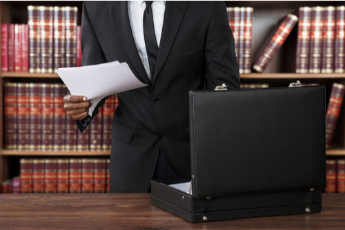 Close-up Of Atlanta brain injury Lawyer putting papers in briefcase