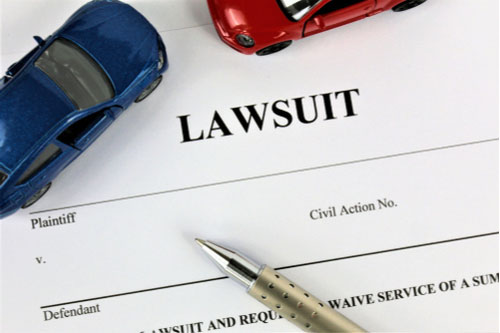 Lawsuit paper with two toy cars