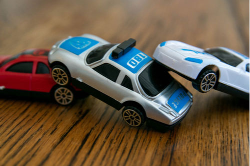 Three plastic toy cars representing chain reaction accident pileup