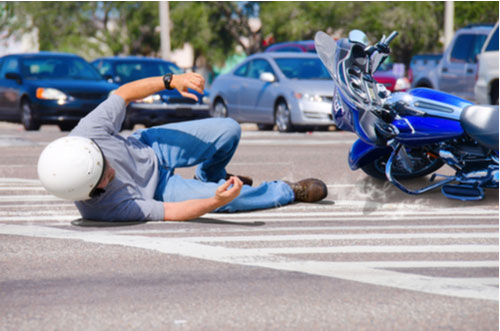 Man falling off motorcycle with motorcycle sliding into traffic