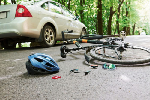 Helmet and bicycle lying on forested road after accident with car