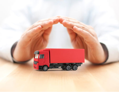 Red toy truck protected by hands, insurance concept