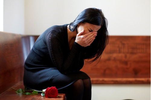grief concept - crying woman with red rose sitting on bench at funeral in church