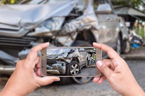 A person taking photos of a car after an accident.