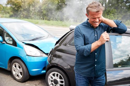 A man getting out of a car holding his neck after being rear-ended.