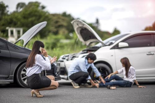 A man checking a woman's leg injury after a car accident.