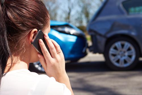 A woman calling the police to report a car accident.