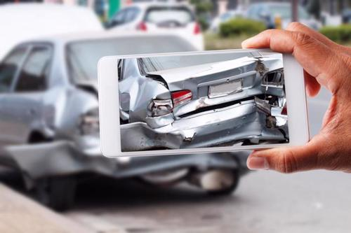A person taking photos of their car after an accident in Perry, Georgia.